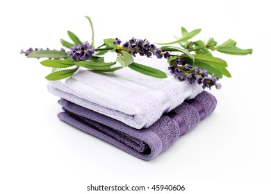 clean towels with lavender flowers on white- beauty treatment
