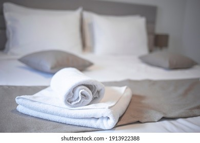 Clean towels on bed at hotel room. Bed maid-up with clean white pillows and bed sheets in beauty bedroom. Close-up. interior background. Towel in Hotel Room , Welcome guests , Room service