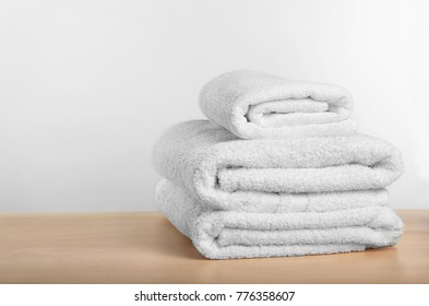 Clean towels on table against light background