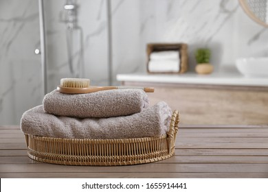 Clean towels and shower brush on wooden table in bathroom