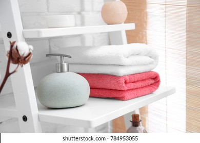 Clean towels with soap dispenser on shelf in bathroom