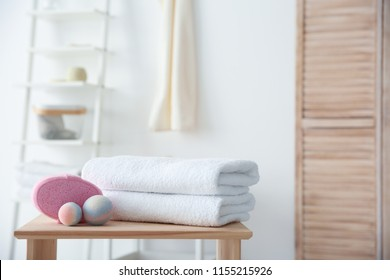 Clean towels and toiletries on table against blurred background