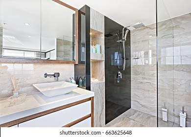 Clean wash room with modern tools, very comfortable  look, perfect lights, glass door can see near walls, ceramic items are shiny