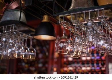 Clean washed glasses hanging over a bar rack