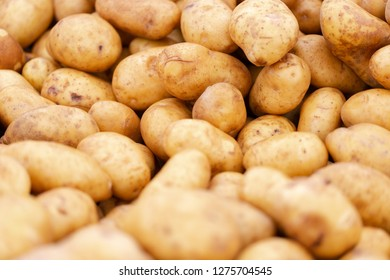 Clean, washed potatoes in light brown, yellow colour on market stall. Full frame close up shoot