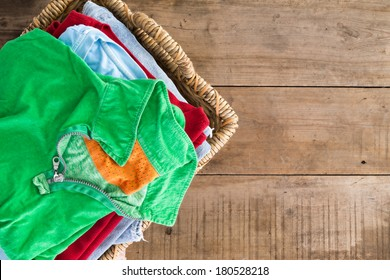 Clean washed unironed summer clothes with a fresh fragrance stacked in a wicker laundry basket with a bright green shirt on top, overhead view on rustic wooden boards with copys pace to the right