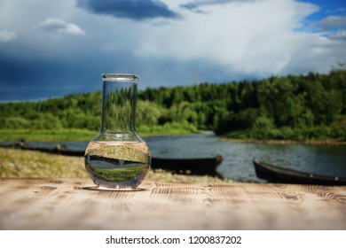 Clean water in a glass laboratory flask on wooden table on mountain river background. Ecological concept, the test of purity and quality of water.