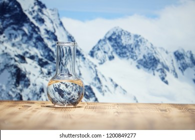 Clean water in a glass laboratory flask on wooden table on winter mountain background. Ecological concept, the test of purity and quality of water.