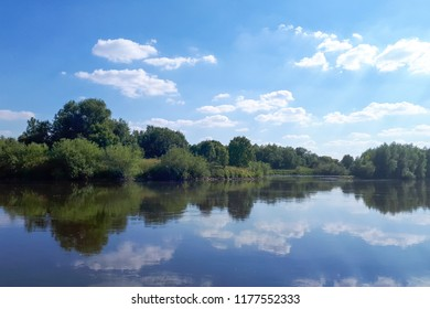 Clean water in the river. The water mirror reflects white clouds. A beautiful view on a sunny day.