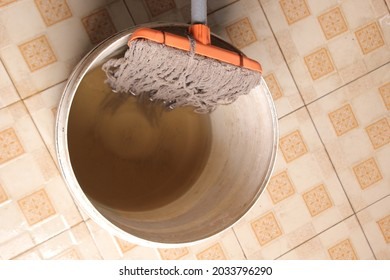 clean the wet floor with a mop and a white bucket with laundry water. mop in a bucket. top view