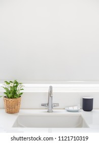 Clean White Bathroom Interior with Sink Basin Faucet, Flower in Weave Pot, Soap and Ceramic Mug. Vertical Image of Modern Design of Bathroom with Copy Space.