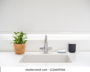 Clean White Bathroom Interior with Sink Basin Faucet, Flower in Weave Pot, Soap and Ceramic Mug. Modern Design of Bathroom with Copy Space.