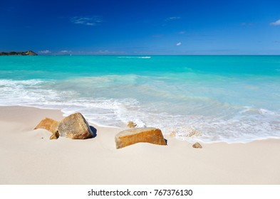 A clean white caribbean beach with deep blue sky and turquoise water, some stones in the foreground. Fort Beach in Antigua.
