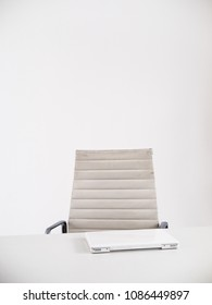 Clean white desk with chair and white laptop, minimalistic shot