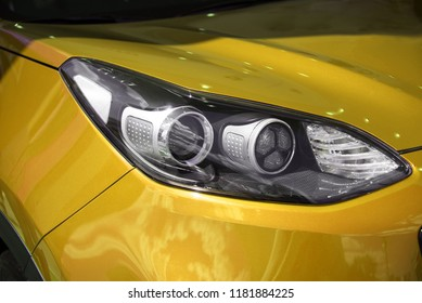clean white headlight of a new yellow luxury car from the saloon. close-up of the front left headlight