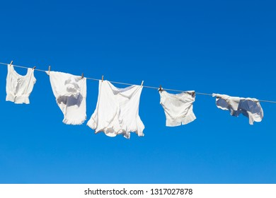 Clean white laundry hanging to dry on a rope against the blue sky during a beautiful sunny day