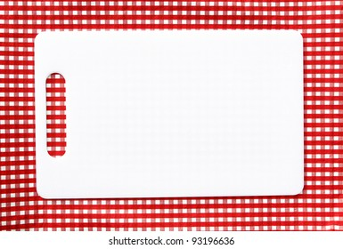 Clean White Plastic Cutting Board isolated on red and white checkered background
