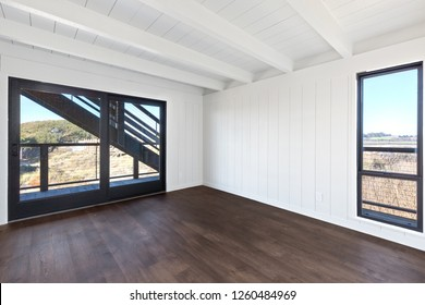 Clean White Room with Hardwood Floors and large windows