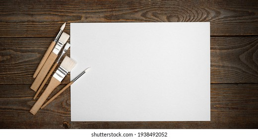 A clean white sheet and brushes on a wood textured background with space to copy. Layout, mockup space for text and drawing.