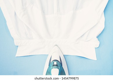 Clean white shirt and iron, blue ironing board, closeup, top view, toned. Concept housework