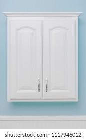 Clean white storage cabinet, floating mount, light blue wall paint, white beadboard or wainscoting