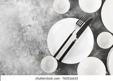 Clean white tableware on a gray background. Top view, copy space