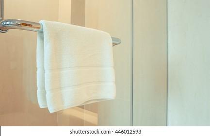 Clean white towel hanging on hanger or handle of glass door
