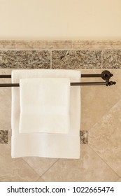 Clean white towels hanging on bronze towel bars in luxury upscale home spa bathroom with stone and tile wall details