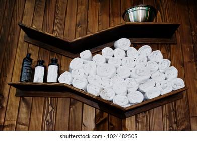 Clean white towels on the shelf in barbershop.