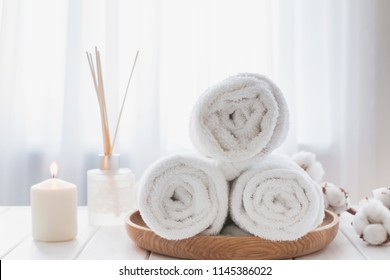 Clean white towels on the wooden tray, candle and aroma diffuser. Spa or bath essentials close-up.