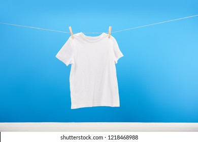 clean white t-shirt hanging on clothesline on blue