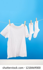 clean white t-shirt and socks hanging on clothesline on blue