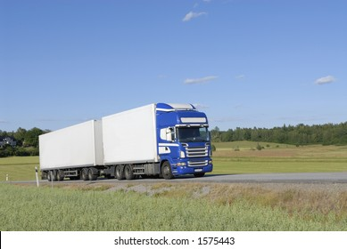 clean white/blue lorry, truck in profile in green countryside