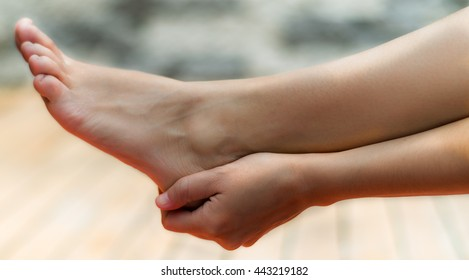 Clean woman foot and her right hand touching her heel, background of wood and stone