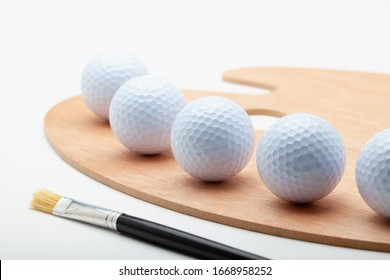 Clean wooden art palette with white golf ball and one brush isolated on white background.