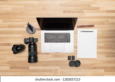 A clean wooden desk with a DSLR photocamera, a lens, a penholder, a laptop and a clear notepad.
