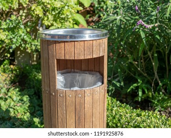Clean wooden and steel trashcan outside at a park area