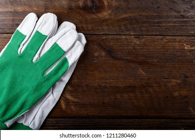clean working gloves white-green on a brown wooden table. place for text