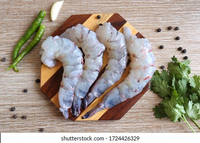 Cleaned, Peeled & Deveined Tiger Prawns or Asian tiger Shrimps. Also known as Kolambi or Bagda chingri. Recipe ingredients like pepper, chilies, garlic, curry leaves at background with copy space.