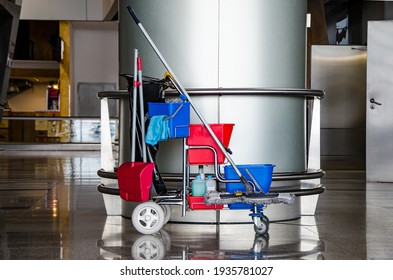 Cleaner cart in a public place. Mobile cart with cleaning products: mop, buckets for cleaning the floor, broom scoop, household chemicals, household rags. Ensuring cleanliness and disinfection.