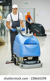 Cleaner male man workers with mop in uniform cleaning corridor pass or hall floor of business building