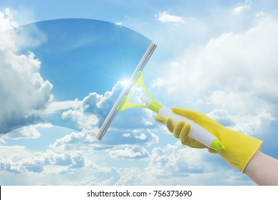 Cleaner washes a window on a background of clouds and sky.