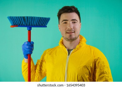 cleaner in a yellow suit in yellow gloves with a broom in her hands on a turquoise background. Cleaning concept