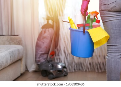 cleaner's hand holds bucket with cleaning products. detergent bottles, sprays, gloves etc, during house cleaning on window background with vacuum cleaner