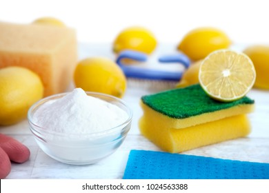 Cleaning accessories with baking soda,sponges and lemon on wooden surface