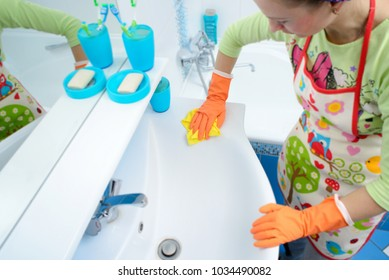 cleaning cleaning bathroom sink and faucet with detergent in rubber gloves with sponge housework