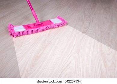 cleaning, before and after concept - close up of wooden floor with pink mop