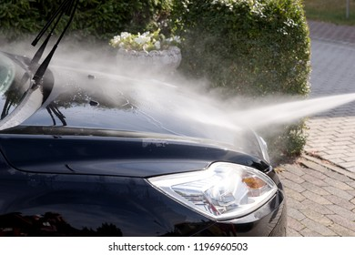Cleaning the black car, car care concept - Car washing under high pressure water