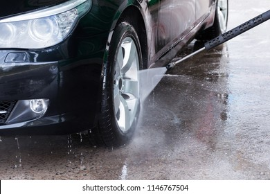 Cleaning black car with high pressure water. Manual car wash with pressurized water in car wash outdoor.