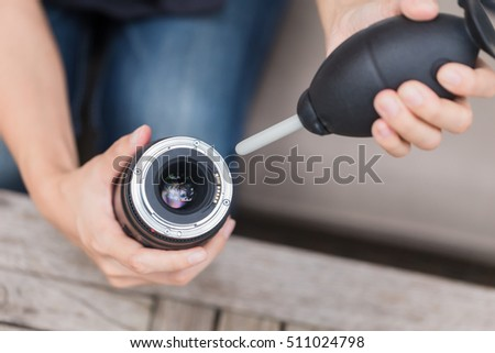 cleaning camera lens with air blower.